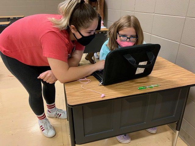 Staff assisting a student with remote learning